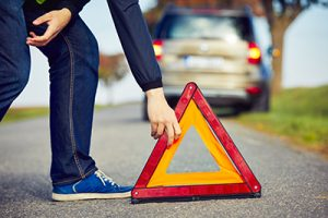 stranded driver putting alert sign behind broken down car | Milwaukee Motor Vehicle Accident Lawyers