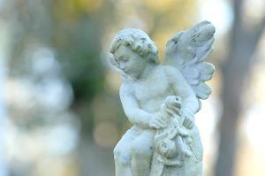 peaceful cherub on top of tombstone in graveyard | Milwaukee Wrongful Death Attorneys