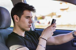 Inattentive Handsome Young Man Busy with his Mobile Phone While Driving a Car | Milwaukee Distracted Driving Accident Attorneys