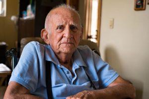 senior man in blue shirt sitting in chair | Milwaukee Elder Abuse Attorneys
