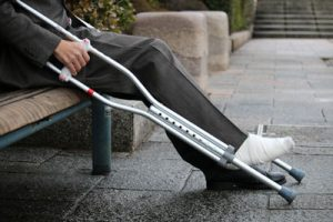 man sitting on park bench with foot in cast and crutches | Milwaukee Pedestrian Accident Attorneys
