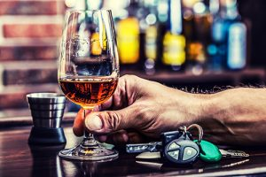 man's hand on bar holding glass of whiskey next to car keys | Wisconsin's Drinking Culture