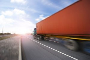 orange semi truck speeding down the highway from the side | Common Trucking Accident Questions