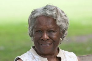 Elderly black woman with gray hair smiling in open grass park | Milwaukee Assisted Living Abuse Attorneys