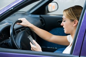 Young woman using cell phone while driving car | Dangers of Texting While Driving