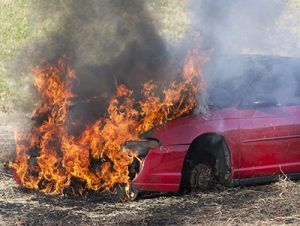 Red car on fire with flames coming out of engine hood in outside area