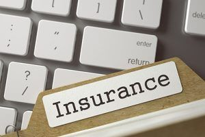 Insurance Folder Laying On Top of Computer Keyboard | Milwaukee Bad Faith Insurance Lawyers