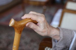 elderly man's hand on a wooden cane | Milwaukee Nursing Home Abuse Attorneys