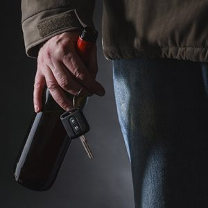 Man in brown jacket holding a beer bottle and pair of car keys at night | Milwaukee Drunk Driving Accident Attorneys