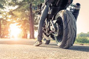 motorcycle from behind with rider's foot touching the ground during sunset in a forest | Milwaukee Motorcycle Accident Attorneys