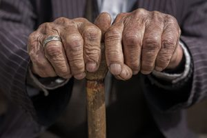 elderly man's hands holding top of cane in dark pinstripe suit wearing gold wedding ring | Wisconsin Elder Abuse Lawyers