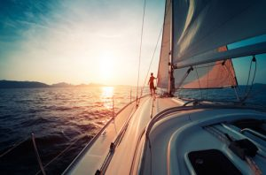 sailboat gliding through water at sunset with man looking into sun | Milwaukee boating accident attorney