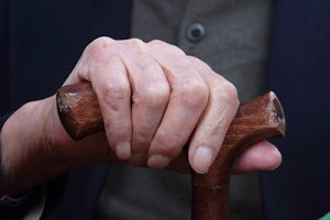 elderly hand on dark wooden cane| Milwaukee Nursing Home Injury Attorney