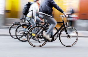 Three men in casual clothes riding bicycles together in city | Milwaukee Bicycle Accident Attorneys