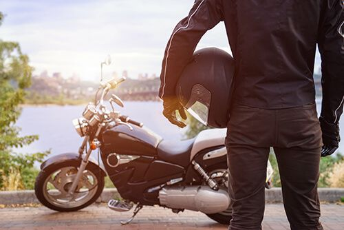 man holding helmet looking at motorcycle by river | How to Choose the Right Motorcycle Helmet