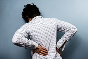 young man holding his back in pain from behind | Newer Model Cars May Cause More Spinal Injuries