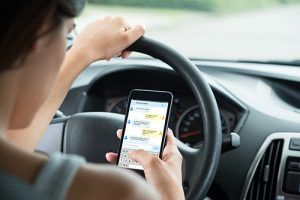 woman checking text messages while driving | Slowing Down to Text