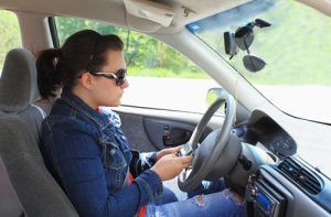 teen girl wearing sunglasses texting while driving | Teens May Be More Likely to Drive Distracted