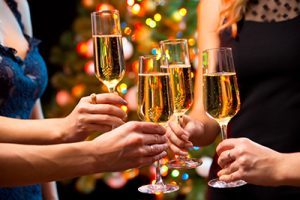 woman at holiday party toasting champagne flutes | Drunk Driving Increases During the Holiday Season