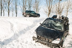 two totaled black cars after an accident on a snowy hillside during the day  | How to Prevent a Car Accident in the Snow
