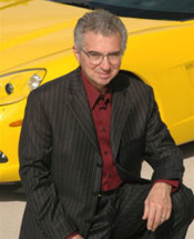 Attorney Vince Menga in black suit posing in front of yellow car